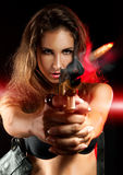 Attractive woman shooting from golden gun Stock Photo