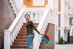Attractive woman   with shopping bags in the ctiy.swings from happiness Stock Photo