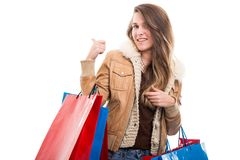 Attractive woman at shopping indicate something behind her. Attractive young woman at shopping indicate something behind her at white background Royalty Free Stock Images