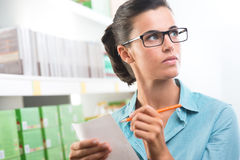 Attractive woman with shopping list. Attractive woman with glasses holding a shopping list at supermarket Stock Images