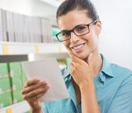 Attractive woman with shopping list. Attractive woman with glasses holding a shopping list at supermarket Stock Photo