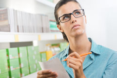 Attractive woman with shopping list. Attractive woman with glasses holding a shopping list at supermarket Royalty Free Stock Image