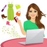 Attractive woman shopping online using a laptop with her credit card buying some fashion goods Royalty Free Stock Photos