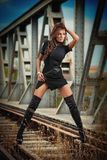 Attractive woman with short black dress and long leather boots standing on the rails with bridge in background. Fashion  sexy girl. On the bridge posing in Royalty Free Stock Images