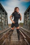 Attractive woman with short black dress and long leather boots standing on the rails with bridge in background. Fashion girl. On the bridge posing in black stock photos