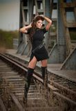 Attractive woman with short black dress and long leather boots standing on the rails with bridge in background. Fashion  sexy girl. On the bridge posing in Stock Images