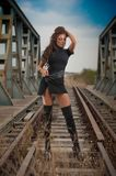 Attractive woman with short black dress and long leather boots standing on the rails with bridge in background. Fashion girl. On the bridge posing in black stock photo