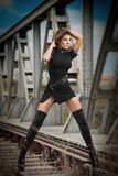 Attractive woman with short black dress and long leather boots standing on the rails with bridge in background. Fashion girl. On the bridge posing in black royalty free stock images