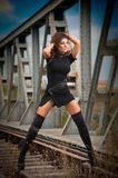 Attractive woman with short black dress and long leather boots standing on the rails with bridge in background. Fashion girl. On the bridge posing in black stock photography