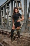 Attractive woman with short black dress and long leather boots standing on the rails with bridge in background. Fashion  sexy girl Royalty Free Stock Images