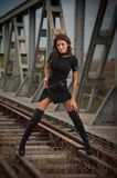 Attractive woman with short black dress and long leather boots standing on the rails with bridge in background. Fashion girl. On the bridge posing in black royalty free stock image