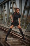 Attractive woman with short black dress and long leather boots standing on the rails with bridge in background. Fashion girl. On the bridge posing in black stock images