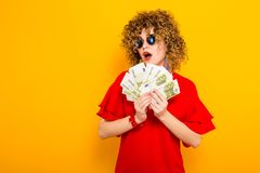 Attractive woman with short curly hair with cash. Portrait of a white surprised woman with afrro hairstyle in red dress and sunglasses holding fan of euro bills Stock Photos