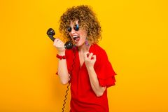 Attractive woman with short curly hair with phone royalty free stock images