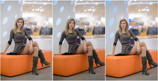 Attractive woman with short dress and long leather boots posing in mall. Beautiful fashionable young girl sitting on orange bench. In modern shopping center Stock Photos