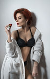 Attractive woman with short red hair in white towel rob over black lingerie holding a strawberry. Side view of perfect body woman Royalty Free Stock Photo