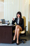 Attractive woman in a short skirt drinking coffee in office Royalty Free Stock Images