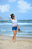 Attractive woman in shorts walking happy on beach sand wearing s stock image