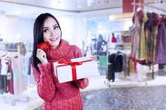 Attractive woman show gift card and present in shopping mall Stock Photos