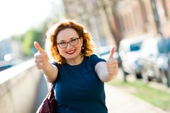 Attractive woman showing gesture with fingers - thumb up royalty free stock image