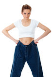 Attractive woman shows her old huge jeans Stock Photo