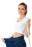 Attractive woman shows her old huge jeans Stock Photography