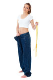 Attractive woman shows her old huge jeans, diet Royalty Free Stock Photography