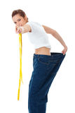 Attractive woman shows her old huge jeans, diet Stock Photo