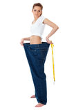 Attractive woman shows her old huge jeans, diet Stock Photography