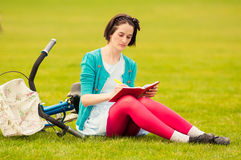 Attractive woman sits on green grass and write on notebook Stock Photography