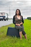Attractive woman sits on staircase near road. Pretty travelling woman with suitcase waiting on road Stock Photography