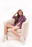 Attractive woman sitting on a armchair Stock Photo