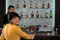Attractive woman sitting at a bar counter. Attractive women sitting at a bar counter turning to look back over her shoulder at the camera with a display of stock photography