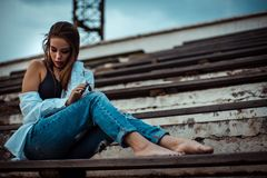 Attractive woman sitting with bare feet in the stadium. She`s wearing a shirt and jeans stock photo