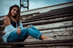 Attractive woman sitting with bare feet in the stadium. She`s wearing a shirt and jeans.  royalty free stock image