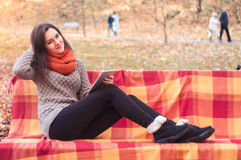 Attractive woman sitting on a bench with a tablet Stock Photos