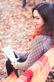 Attractive woman sitting on a bench with a tablet Royalty Free Stock Photos