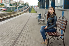 Attractive woman sitting on a bench waiting Stock Image