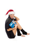 Attractive woman sitting with blue present box. Young attractive woman in Santa hat sitting with present box, isolated Stock Images
