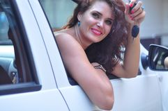 Attractive woman sitting in car showing keys. Close-up portrait happy smiling young beautiful brunette Caucasian woman,  sitting in her white car showing keys Stock Image