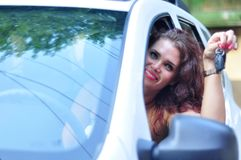Attractive woman sitting in car showing keys. Close-up portrait happy smiling young Caucasian woman  sitting in her white car showing keys. Personal Stock Photos