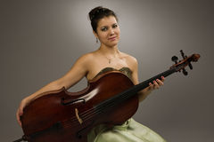 Attractive woman sitting with cello Stock Images