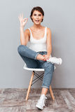 Attractive woman sitting on the chair and showing okay sign Royalty Free Stock Images