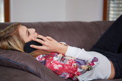 Attractive woman sitting on cosy couch in bright Royalty Free Stock Photos