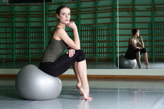 Attractive woman sitting with exercise ball Stock Images