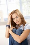 Attractive woman sitting on floor hugging knees Stock Photo
