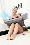 Attractive woman sitting on the floor reading in her home. Royalty Free Stock Image