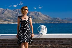 Attractive woman sitting on the Gaeta sea coast. At sunny day Royalty Free Stock Photography