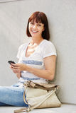 Attractive woman sitting on ground with purse and mobile phone Stock Images