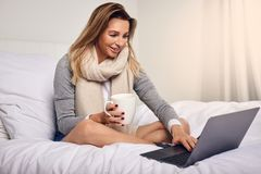 Attractive woman sitting on her bed. Wrapped in a warm knitted scarf with coffee and an open laptop computer smiling at the camera Royalty Free Stock Images